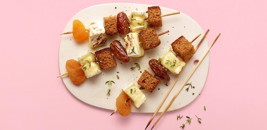 Brochette de brie fondu, pain d'épices, dattes et abricots secs